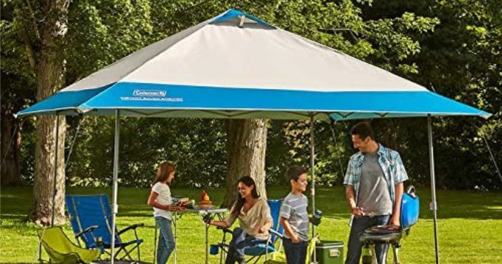 family underneath tan and blue colored Coleman 13' x 13' Instant Eaved Shelter outside
