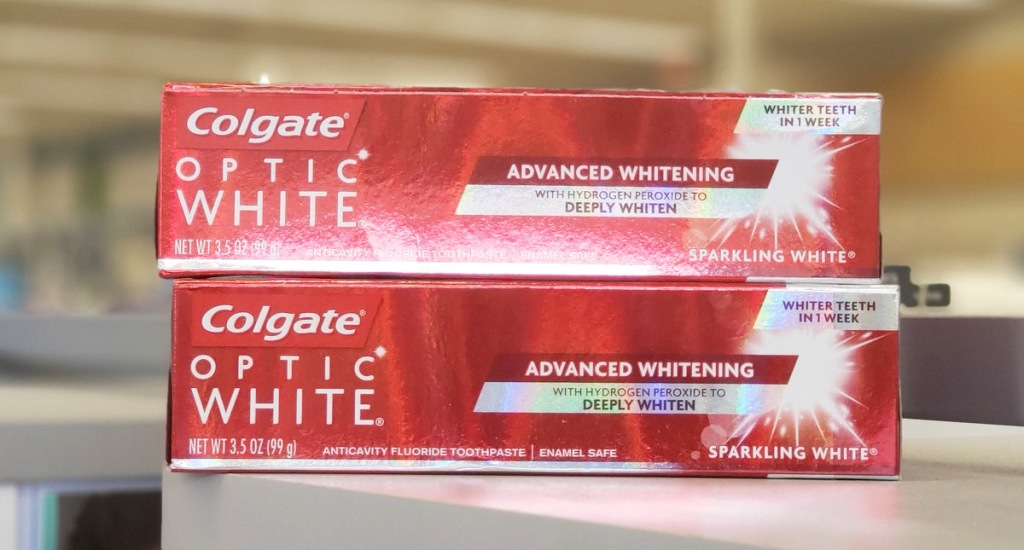 two red boxed of colgate optic white toothpaste stacked on one another