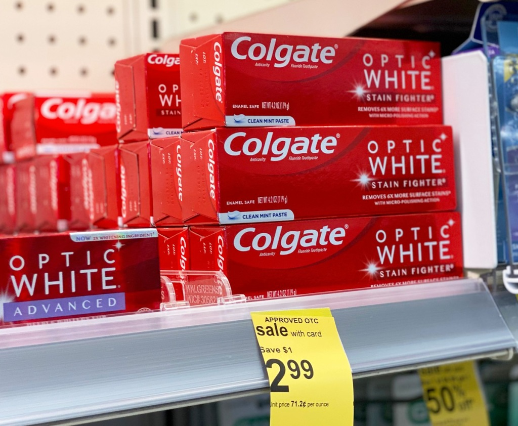 red boxes of colgate optic white toothpaste stacked on a store shelf
