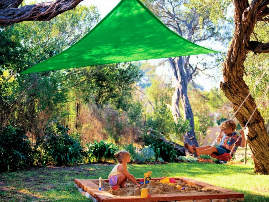 kids playing in yard under a Coolaroo Triangle Shade Sail