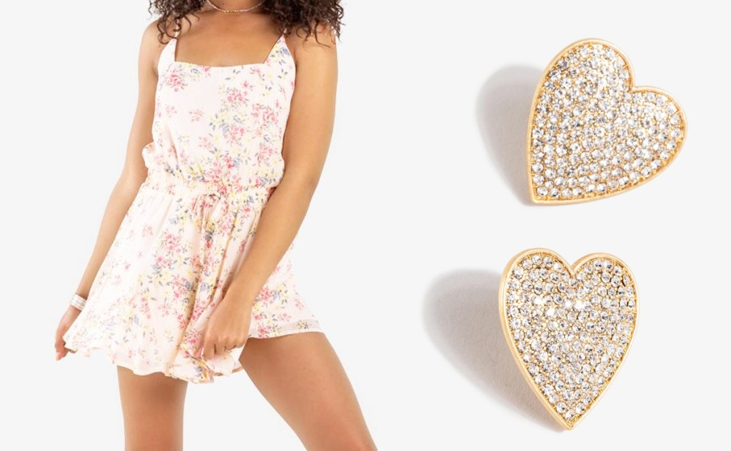 woman in floral print romper with gold heart earrings next to her