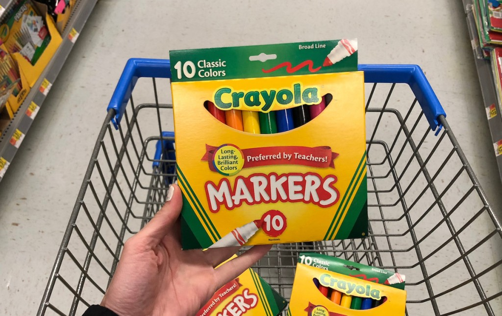 hand holding a pack of crayola markerts with more markers in walmart cart
