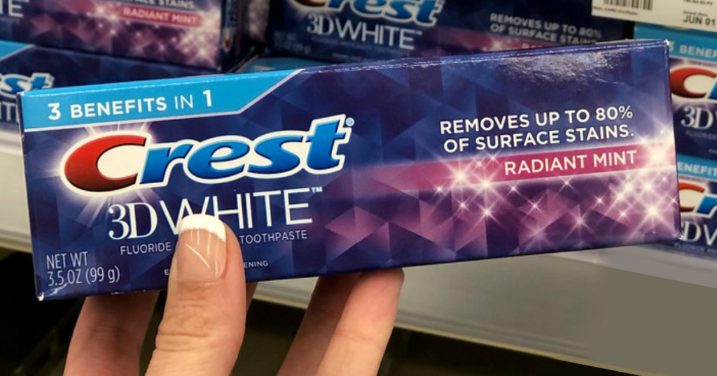 hand holding Crest 3D White toothpaste