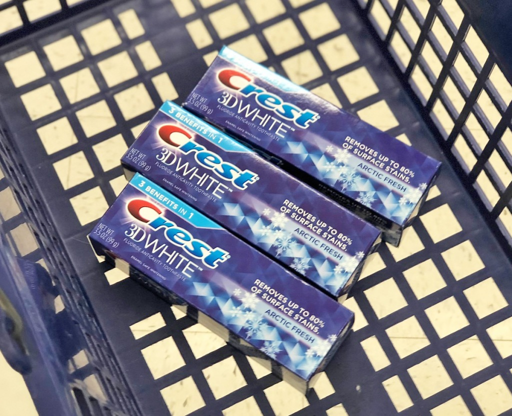 three blue boxes of crest 3d white toothpaste inside the bottom of a blue shopping basket