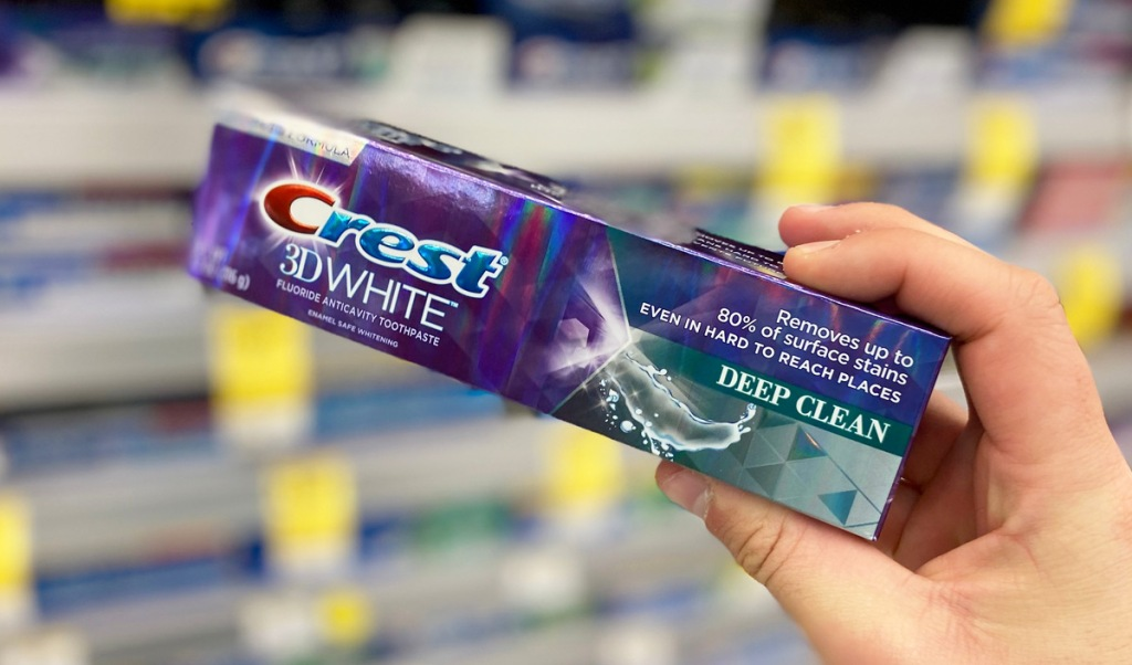 person holding up a purple box of crest 3d white toothpaste