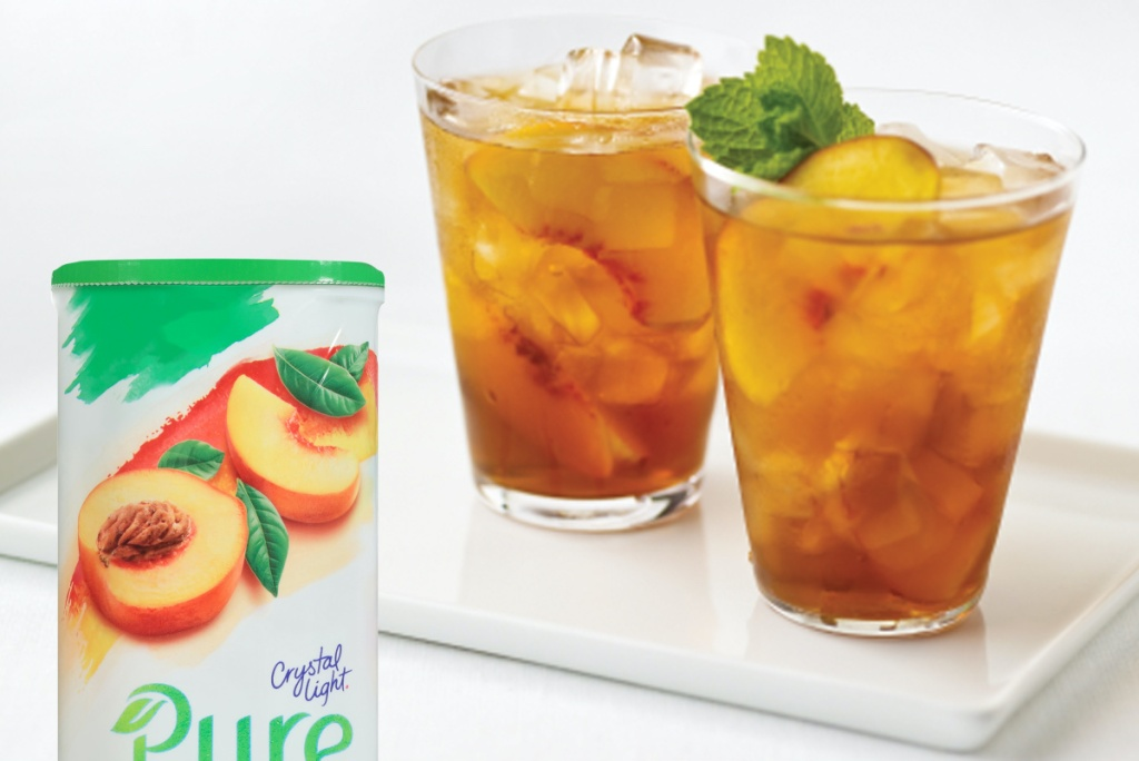 canister of peach iced tea drink mix on white table with two glasses of tea