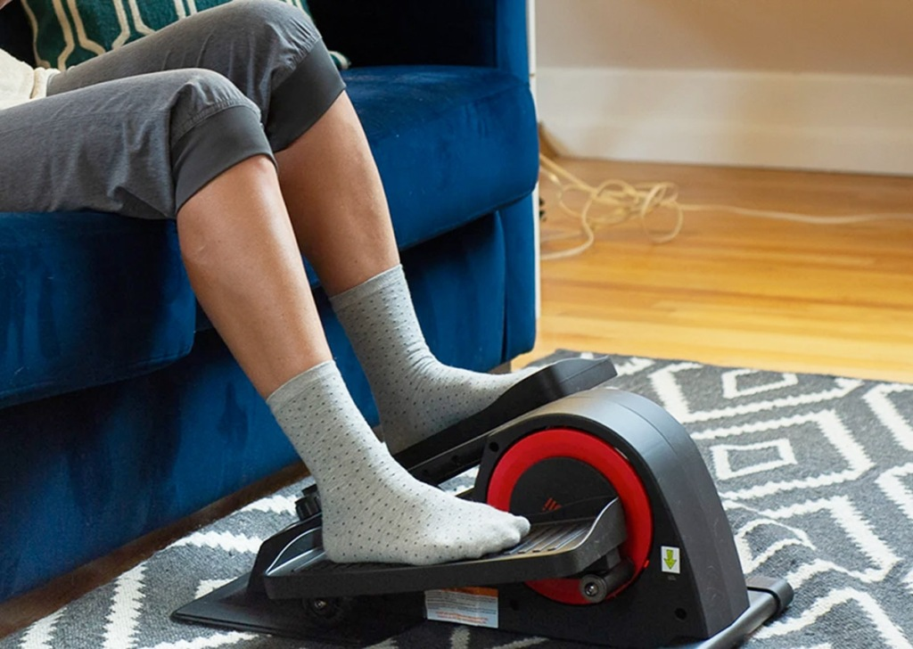 person sitting on blue couch with their feet on a black and red elliptical machine
