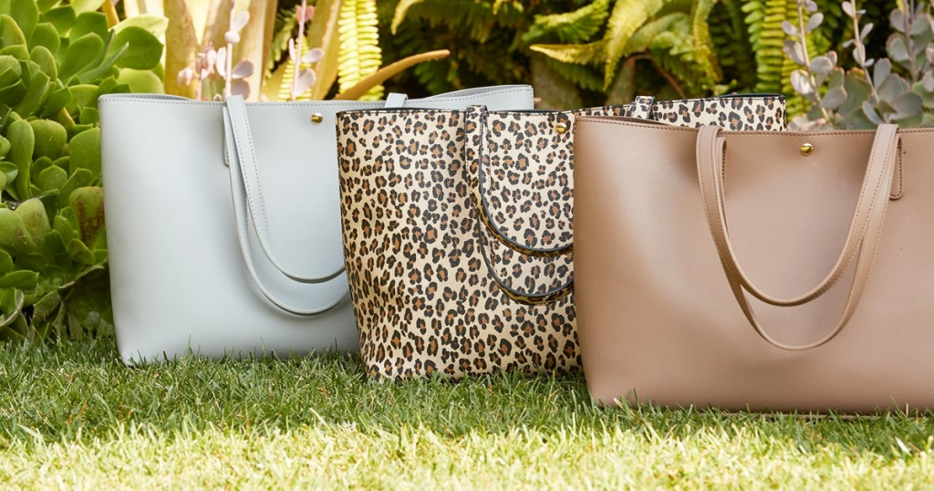 white, leopard print, and brown tote bags sitting on grass