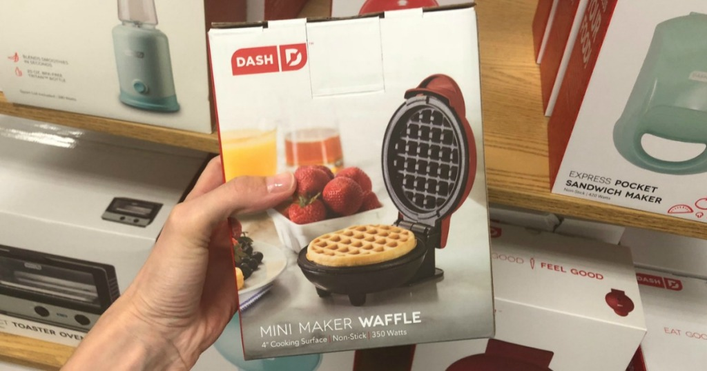 Woman's hand holding a mini waffle maker in the package near an in-store shelf