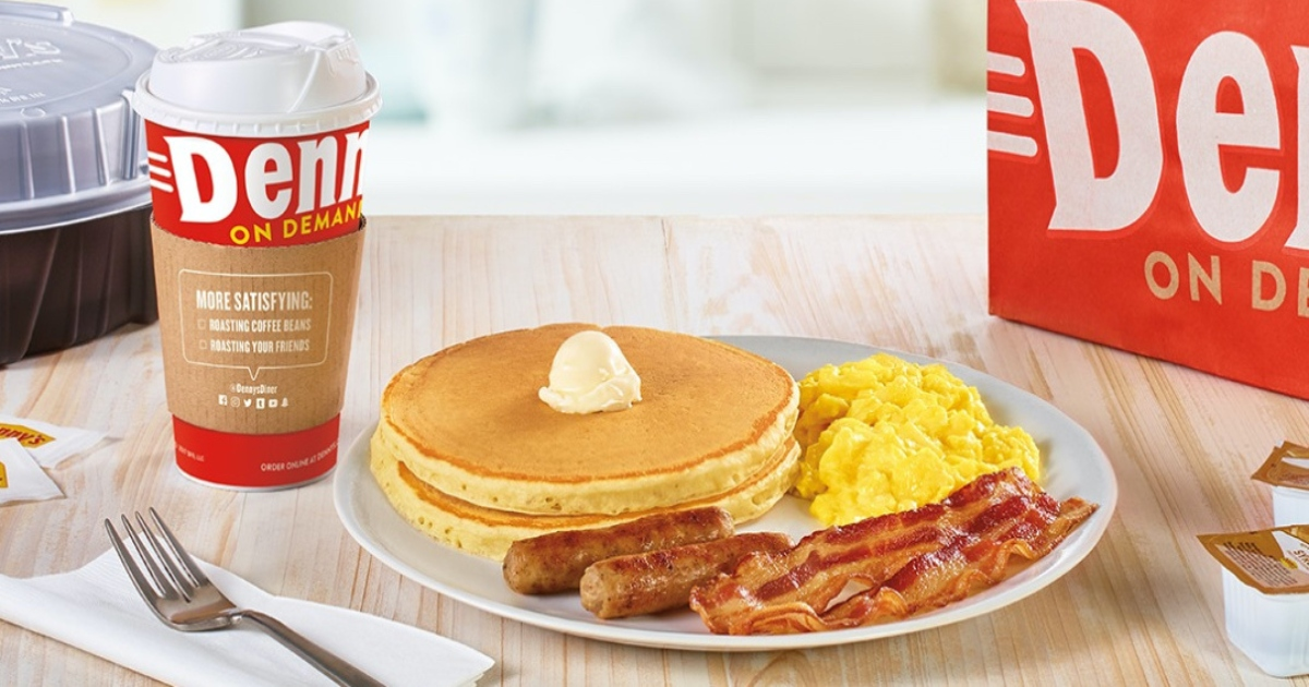 Denny's pancake, eggs and bacon on a plate, with a coffee to go beside it