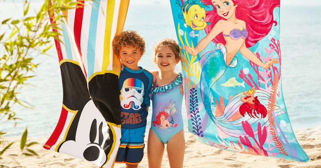 two children on beach with Disney towels