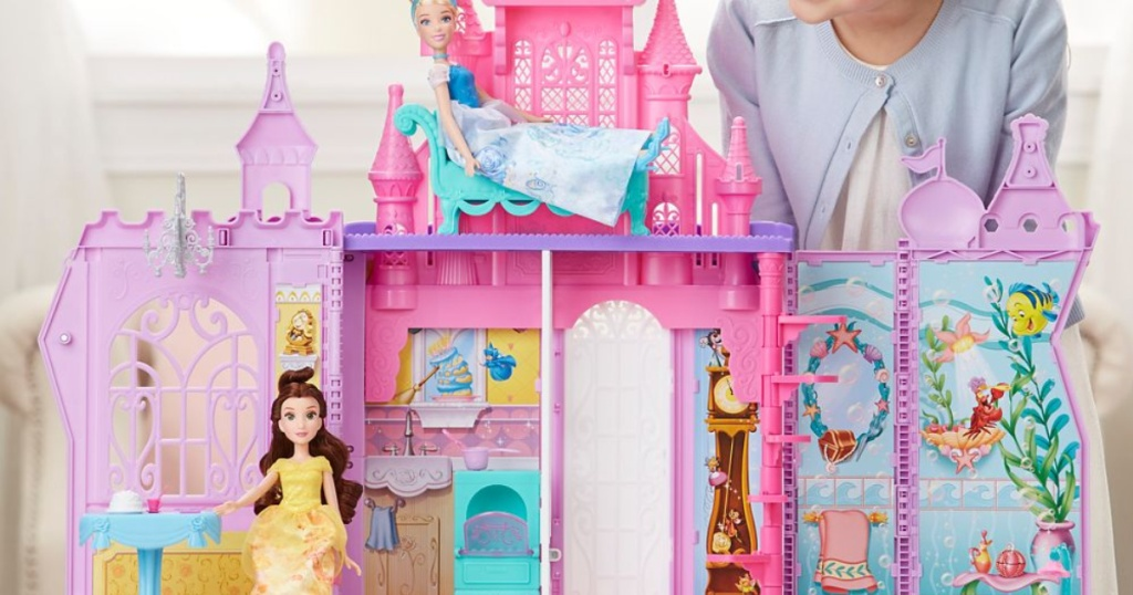 girl playing with large doll palace and dolls