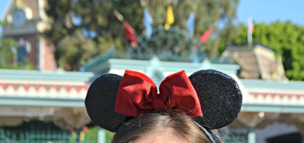 girl with black Mickey Mouse ears and red bow at Disneyland