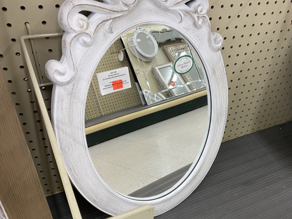 ornate oval white wall mirror in store
