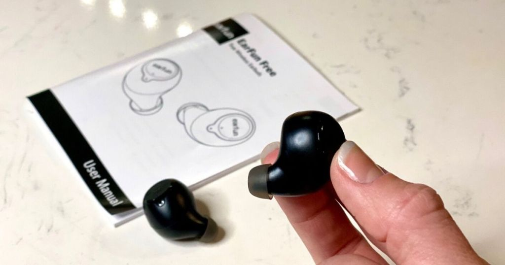 Hand holding an earbud in front of user manual