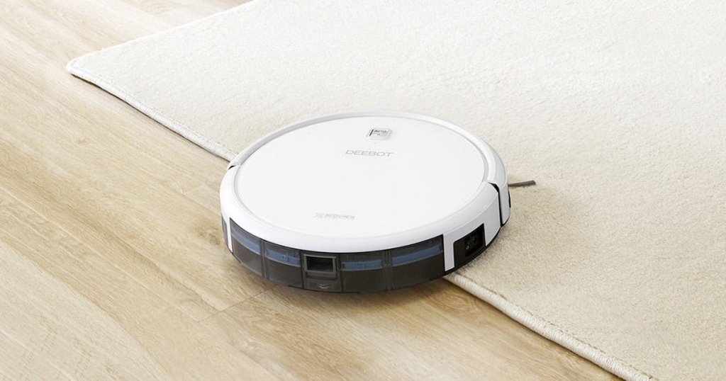 white robotic vacuum on hardwood floor moving onto a cream colored area rug