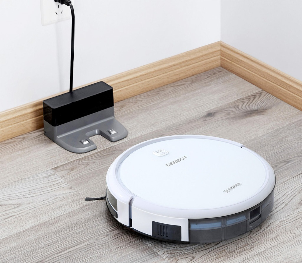 white robot vacuum on hardwood floor heading back to it's charging station