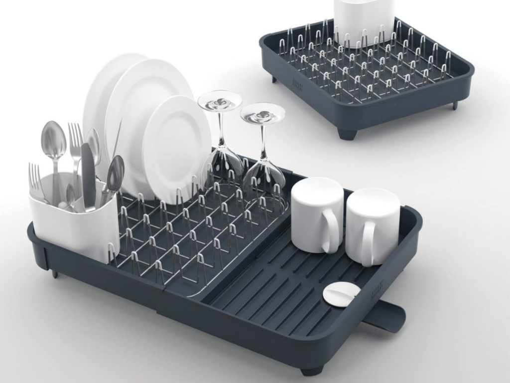 white dishes and silver utensils in gray drying rack
