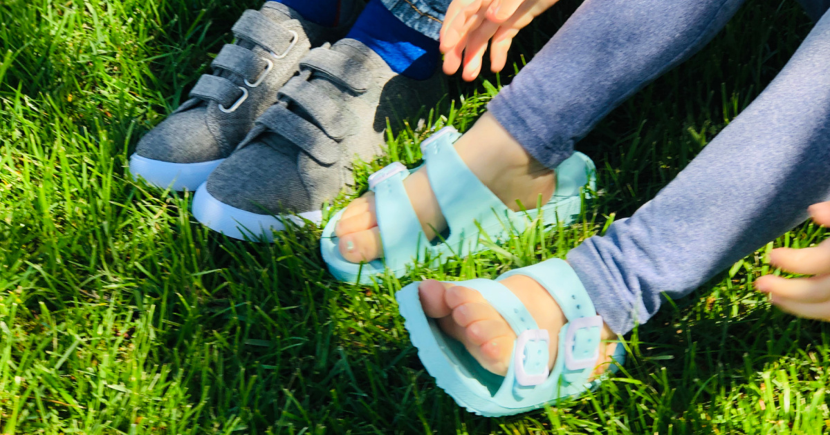 two kids wearing fab kids shoes in blue sandals and grey sneakers