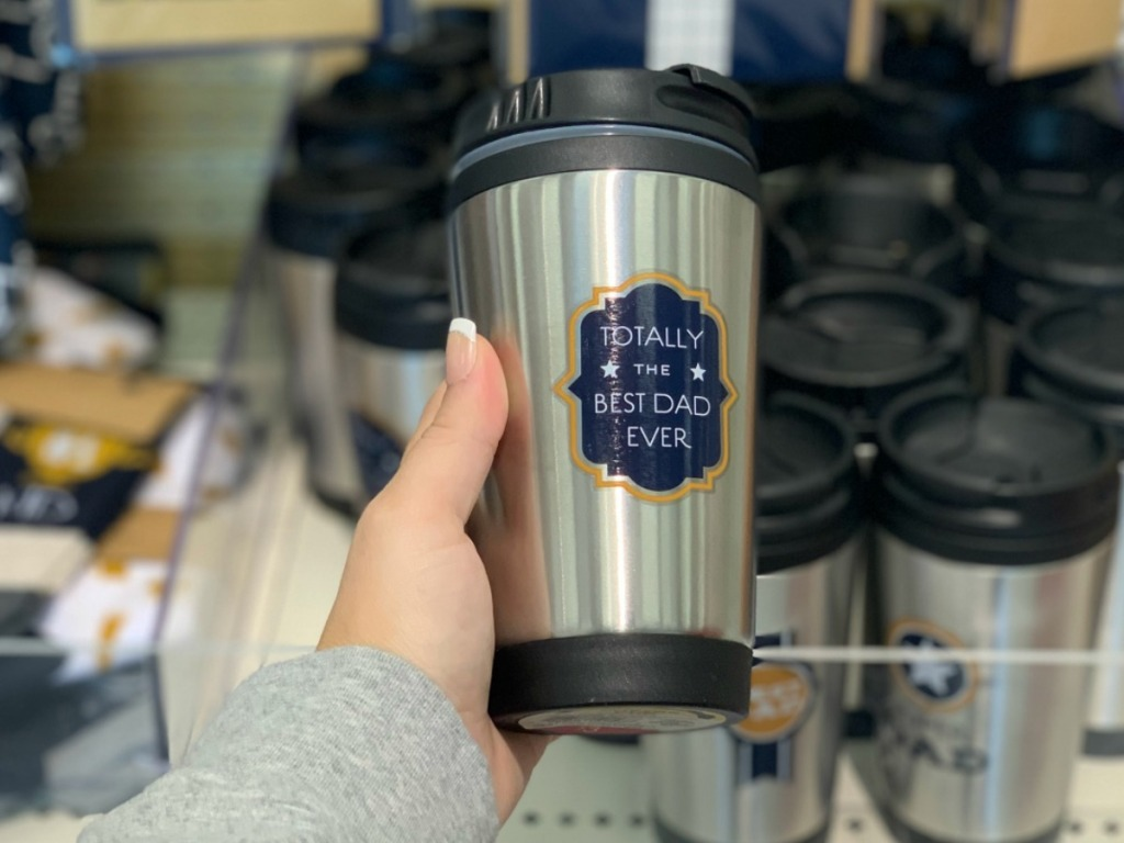 hand holding stainless tumbler by store display