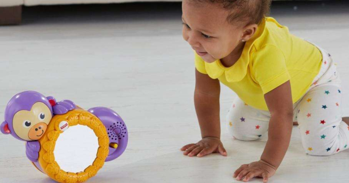 baby wearing a yellow top crawling on the floor behind fisher price monkey toy