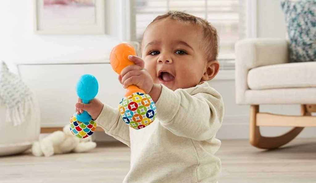 baby sitting on the floor paying with blue and orange Fisher-Price Rattle 'n Rock Maracas