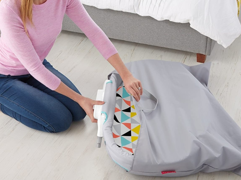 woman on bedroom floor folding away bassinet into bag