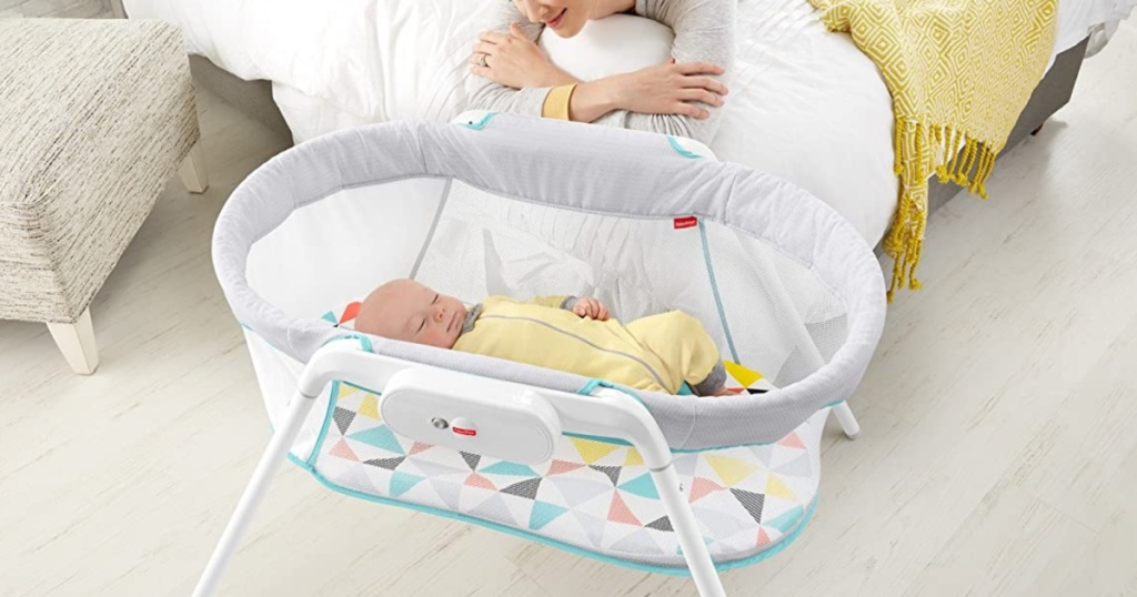 woman laying on bed watching sleeping baby in bassinet