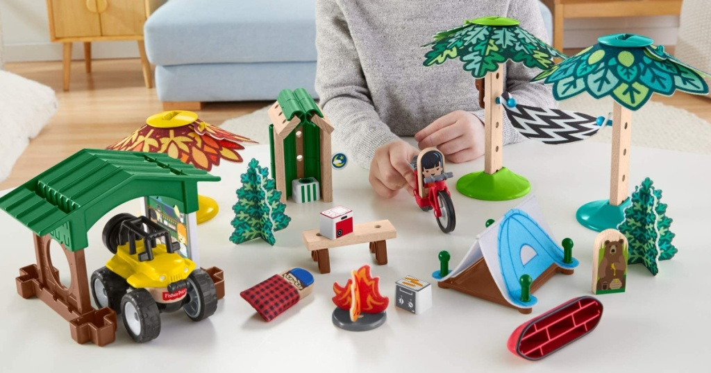 little boy standing at a table playing with a fisher price wonder maker playset