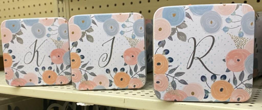 three floral metal monogram boxes on store shelf