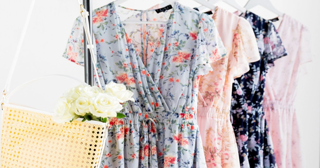 floral rompers on clothing rack with purse and flowers at front