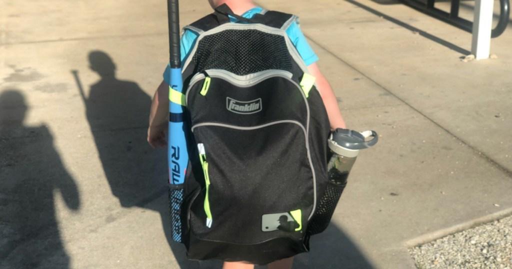 boy walking to baseball with his baseball bag