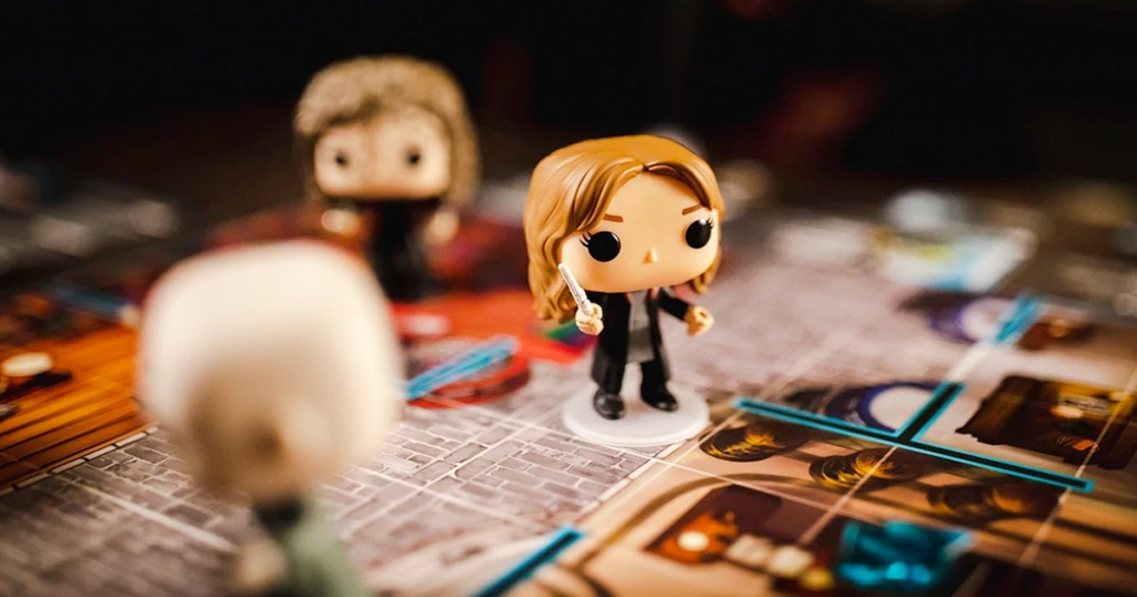 mini funko pop harry potter characters on top of a board game