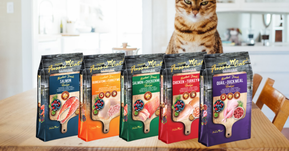 five bags of cat food on wood counter with cat behind them