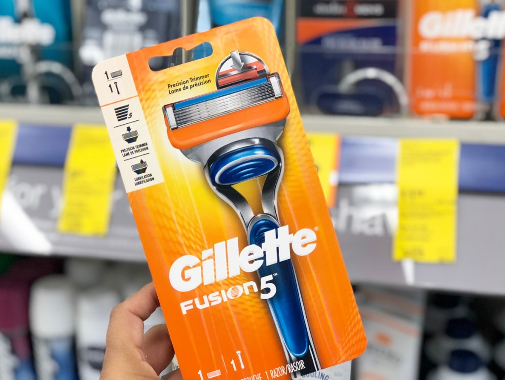 person holding up an orange package for gillette fusion razor in front of razor shelf in store