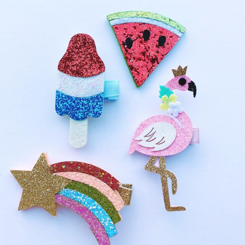 glitter hair clips in the shape of watermelon, shooting star, flamingo, and rocket pop popsicle