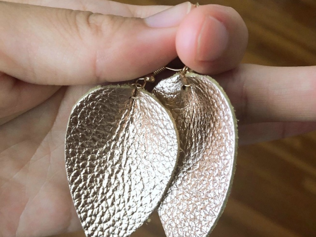 Person holding gold leather earrings