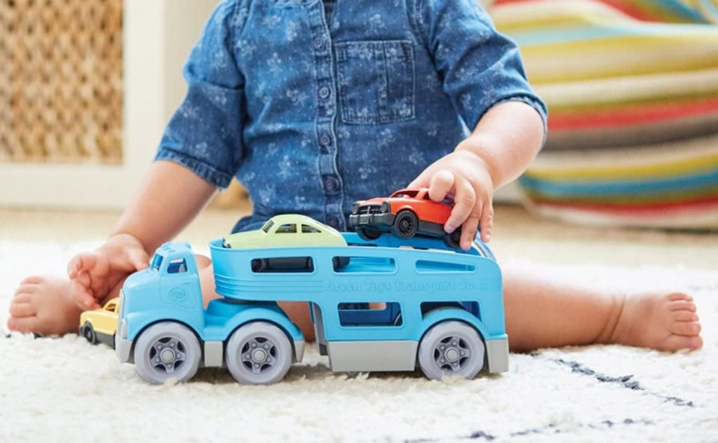 child sitting on rug playing with blue car carrier toy with multiple colors of cars on top