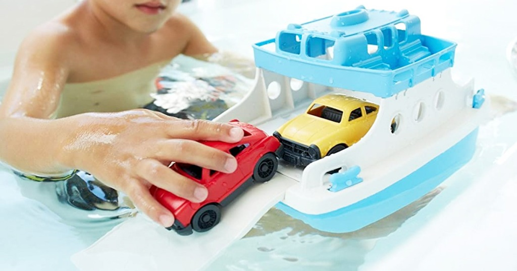 child in bathtub playing with blue and white ferry boat toy and holding red car in hand