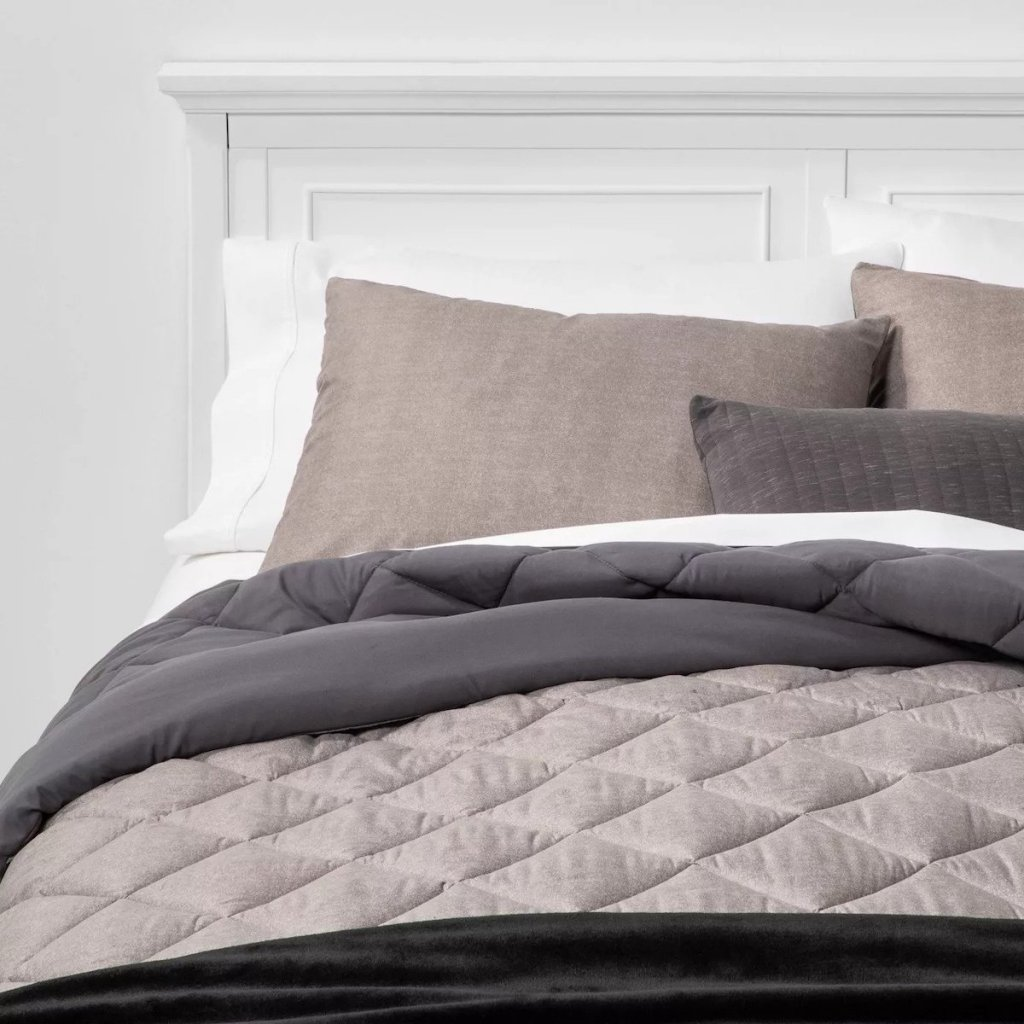 bed with white headboard and grey microfiber comforter and pillows