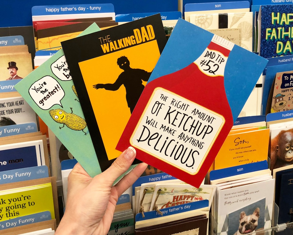 person holding up three father's day greeting cards
