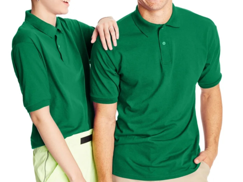 man and woman standing together wearing green short sleeve polo shirts