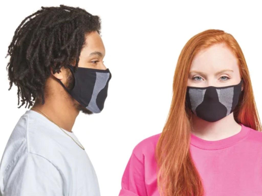 man facing a woman both wearing black and grey face masks
