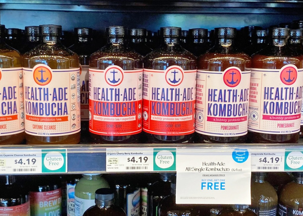 store shelf filled with glass bottles of Health-Ade Kombucha drinks