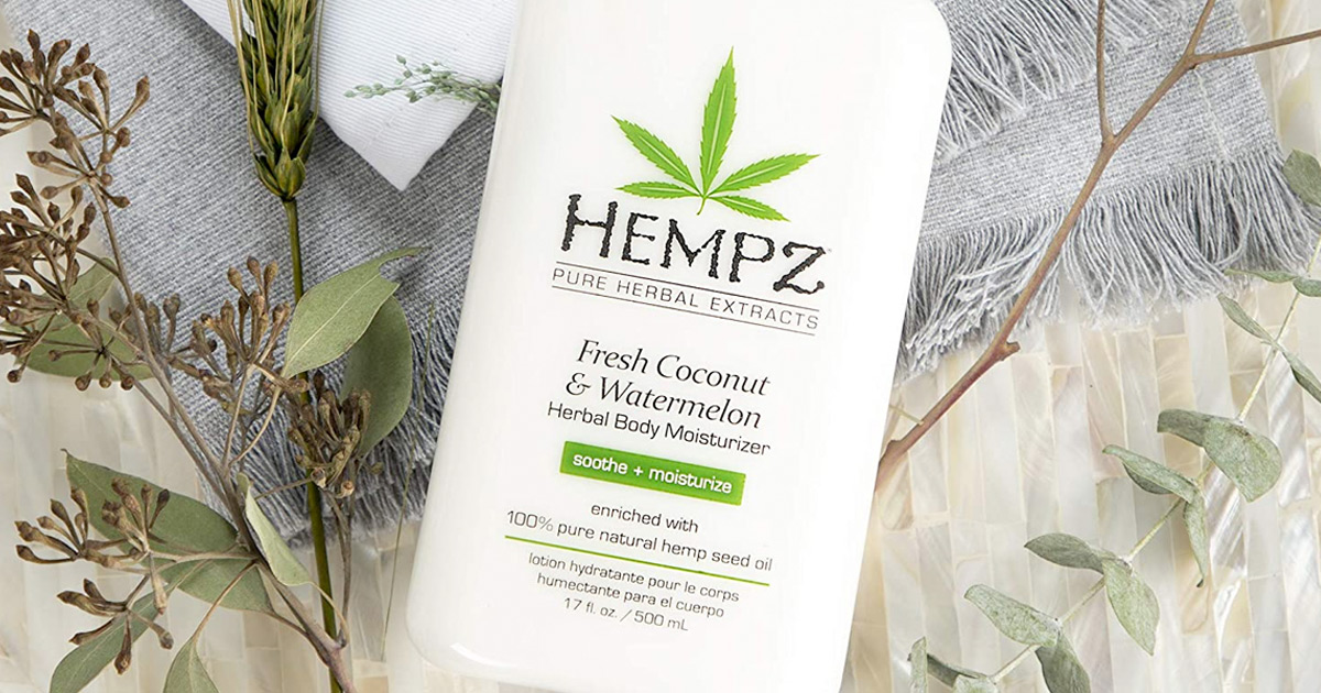 white bottle of Hempz coconut watermelon lotion laying on blanket with leaves around it