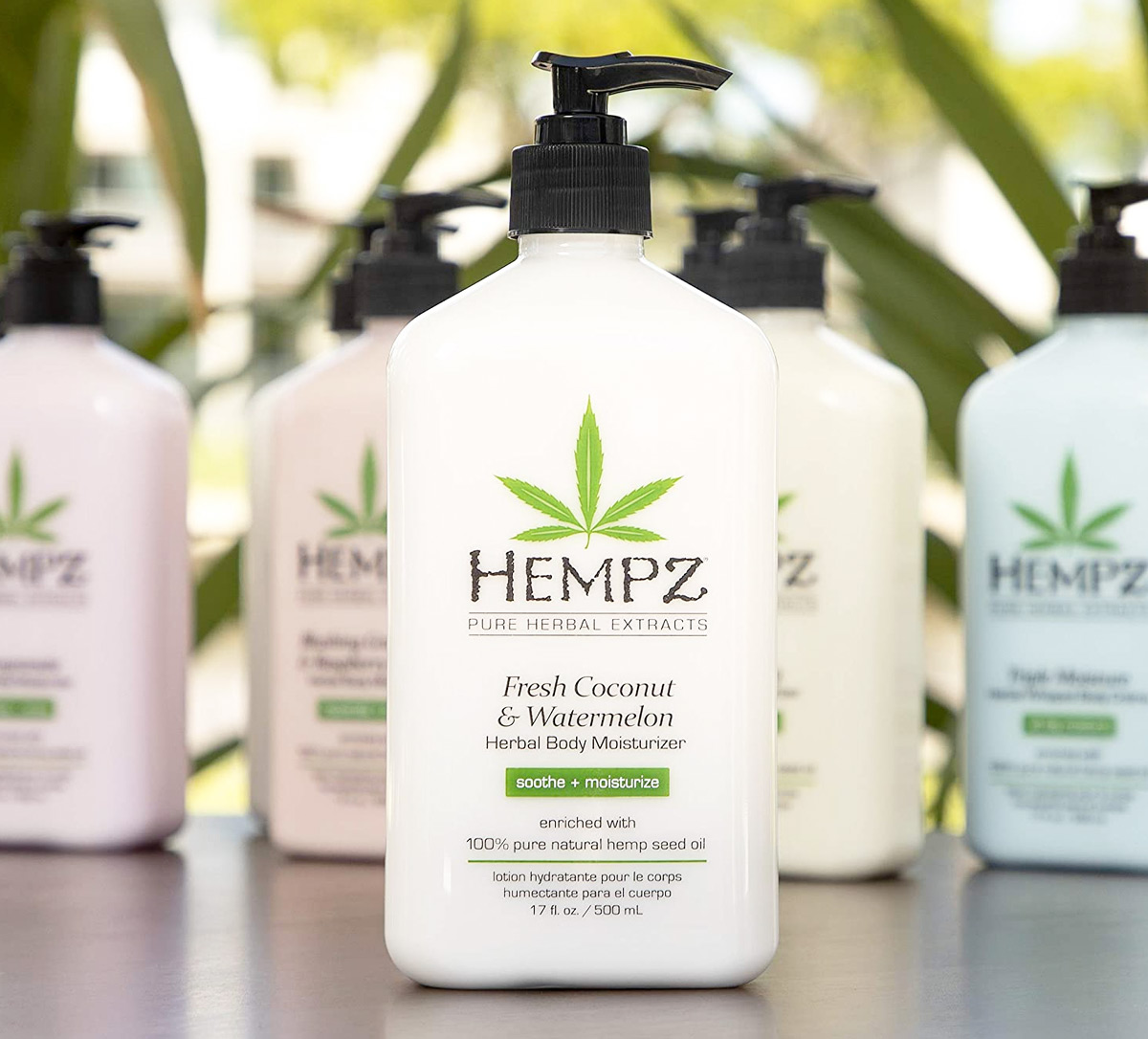 white bottle of Hempz coconut watermelon lotion on table in front of other scents of Hempz lotions