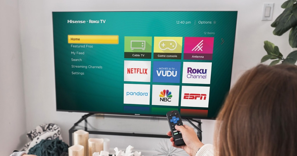 person pointing a roku remote at a smart tv displaying various apps
