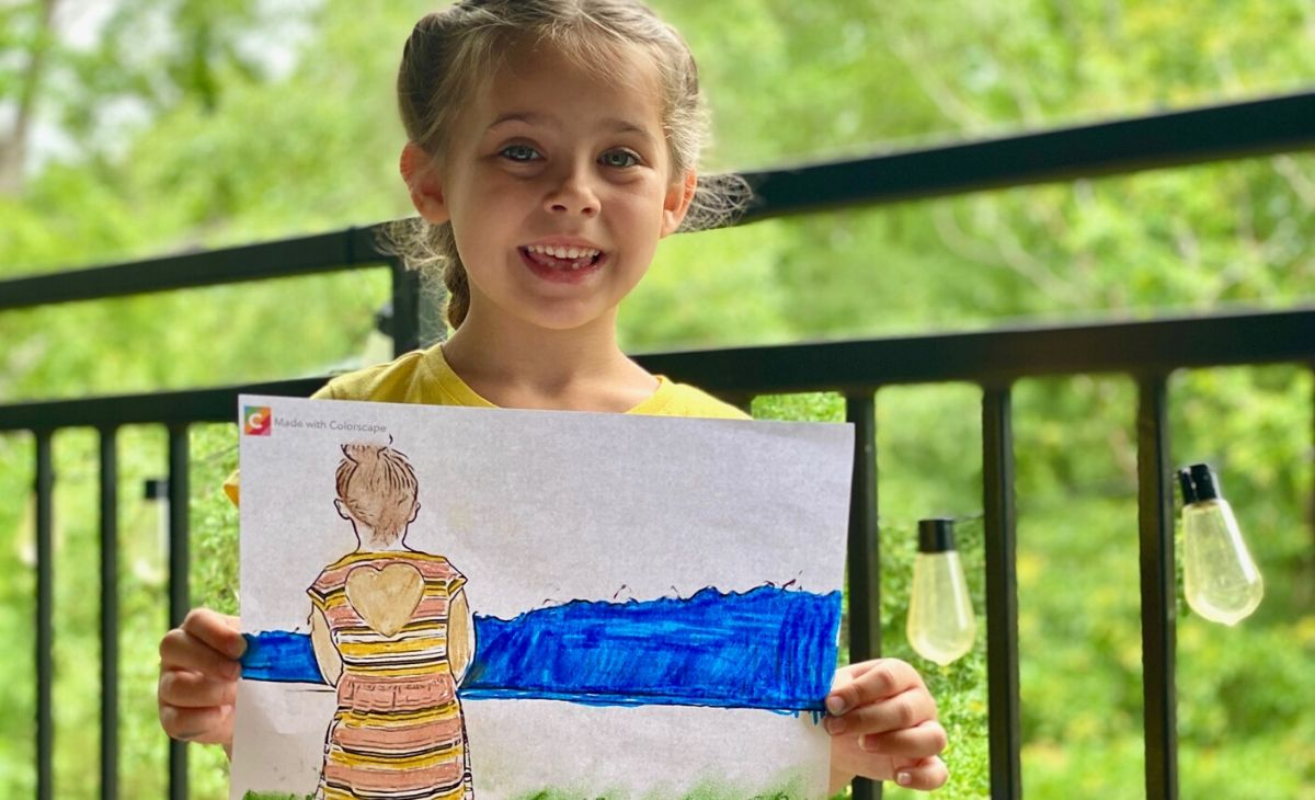 A little girl holding a page colored from a real picture