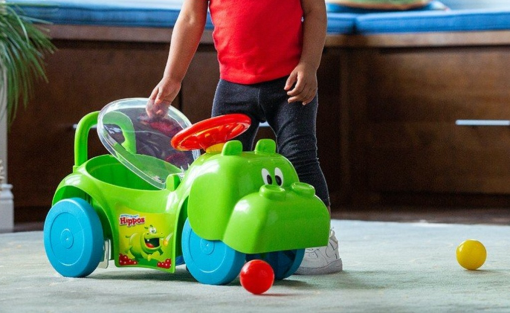 young boy standing next to hippo ride on toy in home