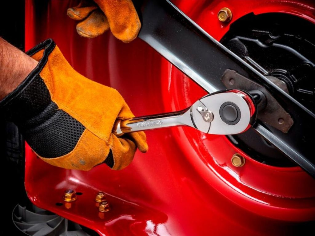 man using socket wrench on car